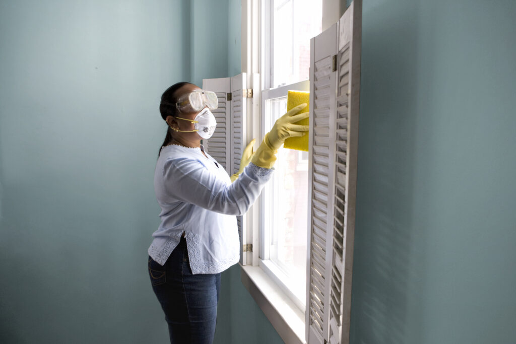 "Woman using a damp sponge to clean dust collected on a window sill. Original image sourced from US Government department: Public Health Image Library, Centers for Disease Control and Prevention. Under US law this image is copyright free, please credit the government department whenever you can""."